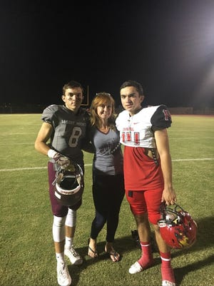 Anthony Chauhan, left, a quarterback at Desert Mountain poses with his brother, Chaparral quarterback Davis Chauhan, and their mother, Ashley, after the Chaparral, Desert Mountain game.