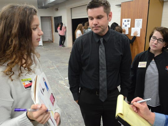 Hillside Middle School teacher Jason Brooks takes a look at some of the costume styles presented by Northville High student Sophie Kenward, left, as Stephanie Rosche, right, joins in as the trio worked at an Oct. 14 drama boot camp at Hillside. The afternoon-long event gave middle school students the opportunity to learn a bit about stage construction, lighting and costumes.
