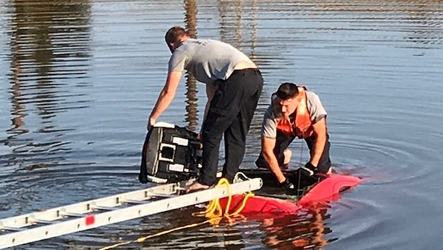 San Carlos Park Fire Department firefighters Barry Johnson and Josh Althouse, in the water, pull an infant car seat from a car found submerged in a canal at the end of Three Oaks Parkway Sunday morning. Nobody was found in the car.