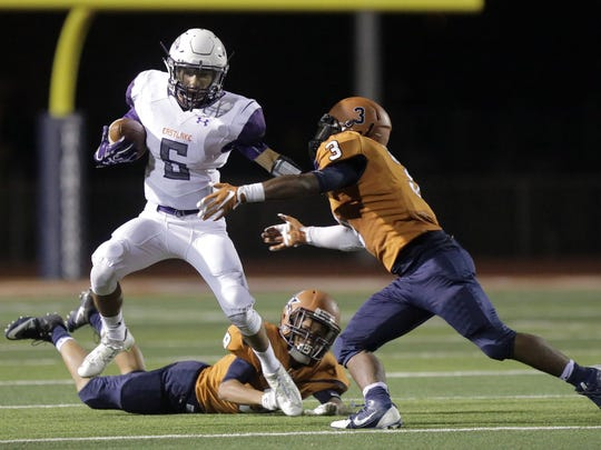 Eastlake's Adrian Talavera stiff arms his way though the Riverside defense as Ian Castillo tries to make the tackle Friday night at Riverside High School.
