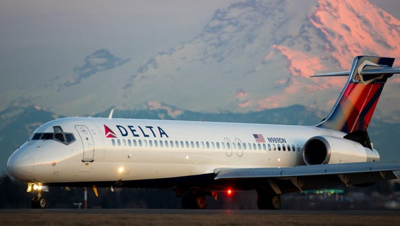 Mt. Rainier looms in the background as a Delta Air
