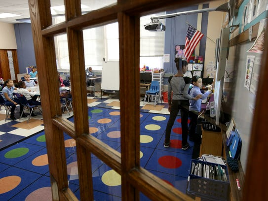 A teacher works with a student at Discovery Charter