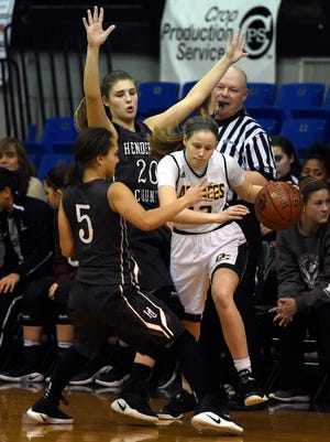 Jalee Carter, left, and Emma Lander of Henderson County try to trap Isabella Henning of Owensboro Catholic during the first quarter of the game at the Owensboro Sportcenter in Owensboro Monday.