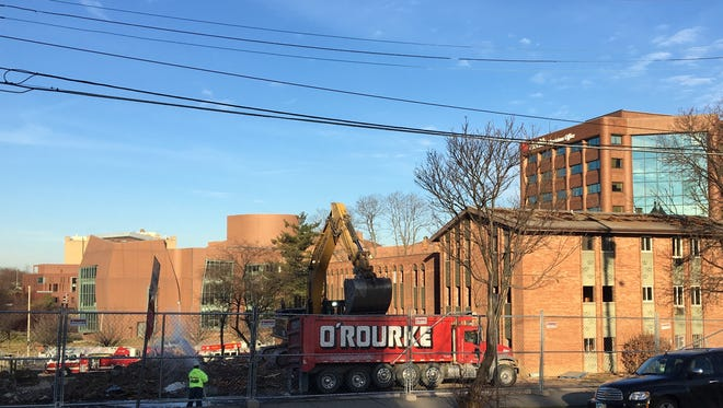 Workers attack the demolishing of the Piedmont Mews apartments on Martin Luther King Jr. Drive between Eden and Bellevue in Corryville. In its place, by 2019, will be the UC Neuroscience Institute.