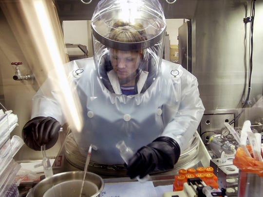 Microbiologist Ruth Bryan works with BG nerve agent simulant at Dugway Proving Ground, Utah, in 2003. The specialized airtight enclosure is also used for hands-on work with anthrax and other deadly agents. Delaware received possible live anthrax spores from the Utah facility.
