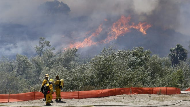 Flames grow as a wildfire burns out-of-control in the north county area of San Diego Tuesday, May 13, 2014.