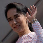 Burma's opposition National League for Democracy party leader Aung San Suu Kyi, with ink still imprinted on the little finger of her left hand after voting, waves after delivering a speech from a balcony of the NLD headquarters in Rangoon, Burma, on Monday, Nov. 9, 2015.