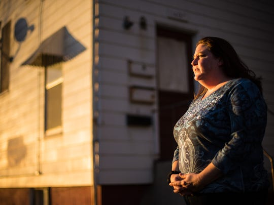 Heather Costello stands in front of the apartment building she moved into last week in Sioux City. The mother of two has been working for a year but living in a homeless shelter.