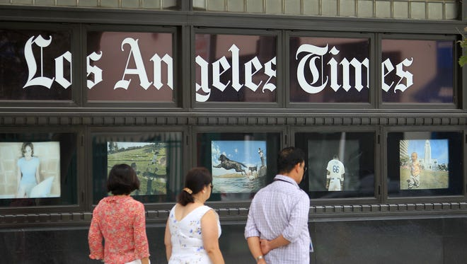 """Pedestrians pass photos displayed on the """"Los Angeles Times"""" building."""