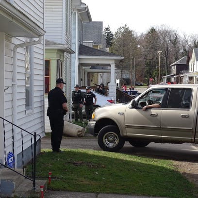 Police surround a home on Cottage Street as part of