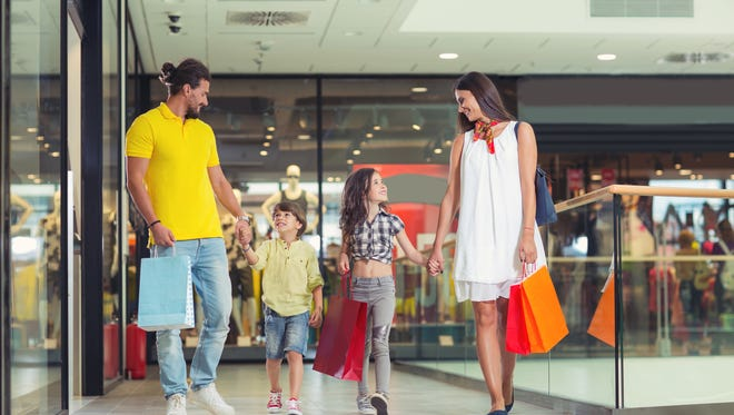 Family with shopping bags holding hands while walking in shopping mall