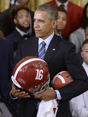 U.S. President Barack Obama holds up an Alabama Crimson Tide helmet jersey and football while welcoming the 2015- 2016 College Football Playoff National Champion Alabama Crimson Tide in the East Room the White House.