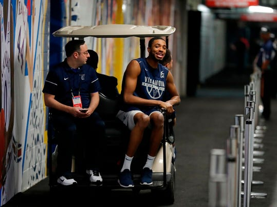 Villanova's Mikal Bridges rides on a cart as he leaves a news conference for the championship game of the Final Four NCAA college basketball tournament against Michigan, Sunday, April 1, 2018, in San Antonio. (AP Photo/Charlie Neibergall)