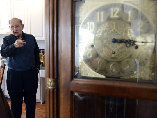 Joe Clark points toward a floor clock in his home Tuesday in Canal Winchester. Clark taught himself to fix clocks in the early 1980s and has been repairing and selling clocks since then.
