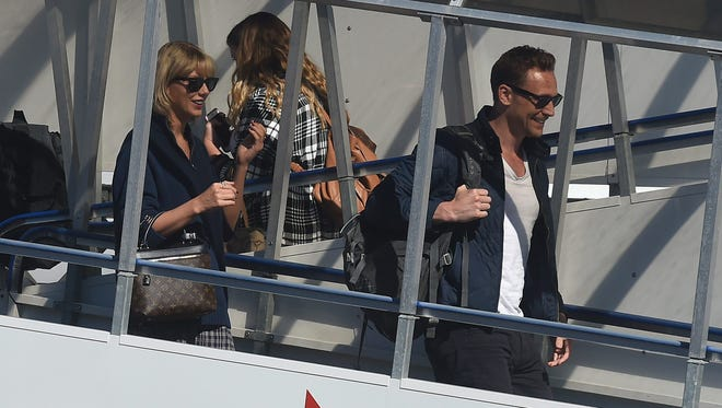 Taylor Swift, left, and Tom Hiddleston arrive at Gold Coast Airport, on the Gold Coast, Queensland, Australia, earlier this month.