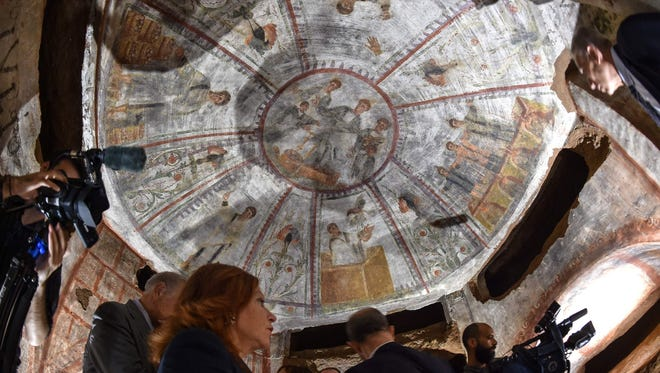 "People look at a fresco, part of the ""dei Fornai"" (bakers) cubicle, during a visit after the restoration of the catacomb of Santa Domitilla, in central Rome, on May 30, 2017."