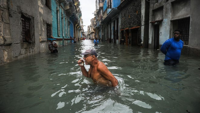 A Cuban wades through a flooded street in Havana, on September 10, 2017.