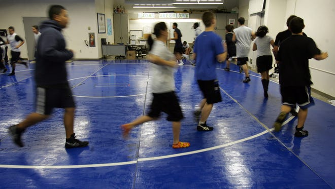 Wrestlers run a mat in this 2009 file photo.