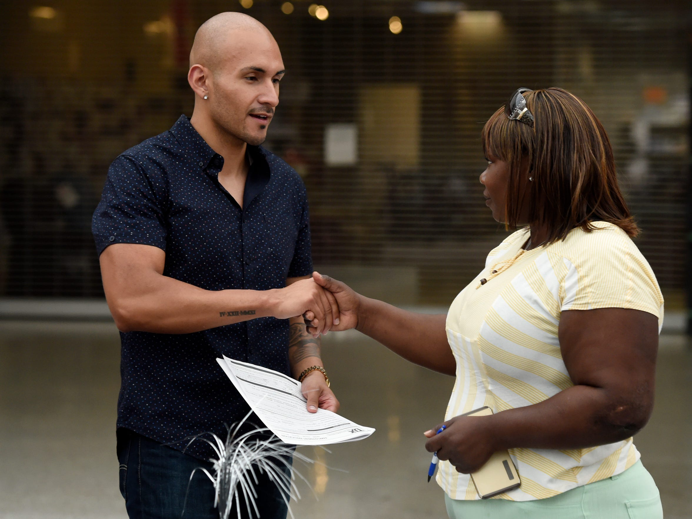 Marianie Sanon shakes hands with Manny Medina after filling out a job application at Washington Square Mall in Evansville recently.   Sanon was one of 21 Haitian passengers injured when the van they were being transported in wrecked on Interstate 69 while traveling to their worksite on Sept., 24, 2015. Two passengers died and several others, including Sanon, were severely injured.