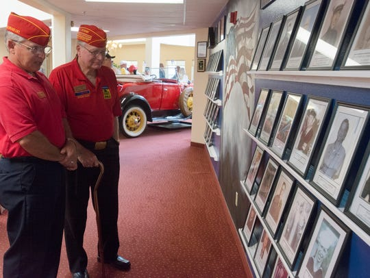 Marine Corps League members Paul Orr, left, and George Dodge look over a display of photos at University Pines in 2016.