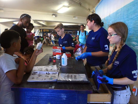 AquaTeens sell temporary tattoos to guests Friday, Aug. 28, 2017, at the Texas State Aquarium in Corpus Christi.