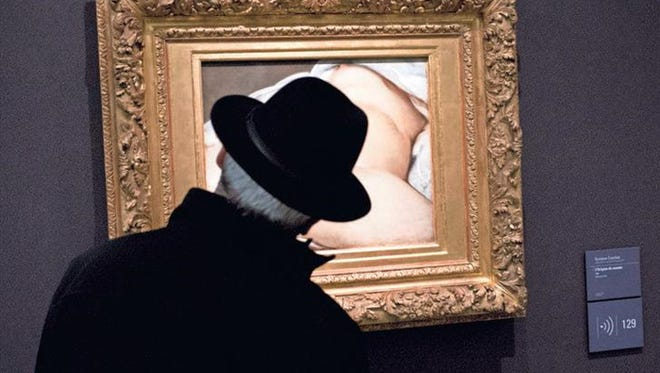 """A visitor looks at Gustave Courbet's 1866 """"The Origin of the World,"""" painting, which depicts female genitalia, Friday at Orsay museum in Paris. Facebook lost a crucial legal battle Friday as a Paris court ruled the social network can be sued in France over its decision to remove the account of a French user who posted a photo of Courbet's famous 19th-century nude painting."""