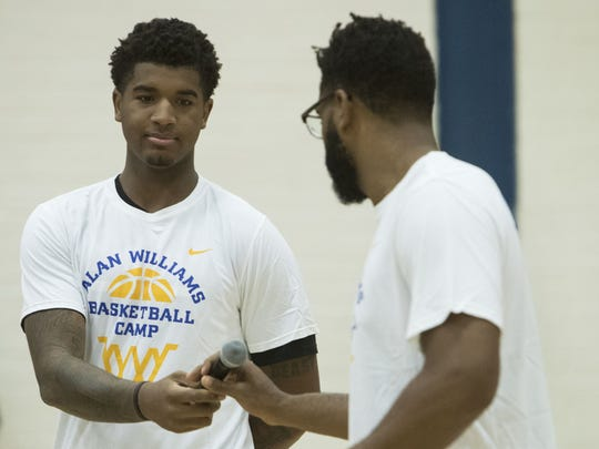 Phoenix Suns' Marquese Chriss hands Alan Williams the microphone at North High School on Aug. 13, 2017 in Phoenix.