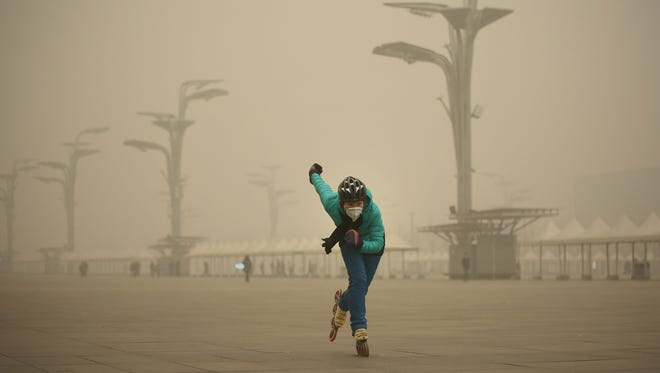 A woman wearing a mask practices roller blading at Olympic Park during heavy smog on Dec. 1, 2015, in Beijing.