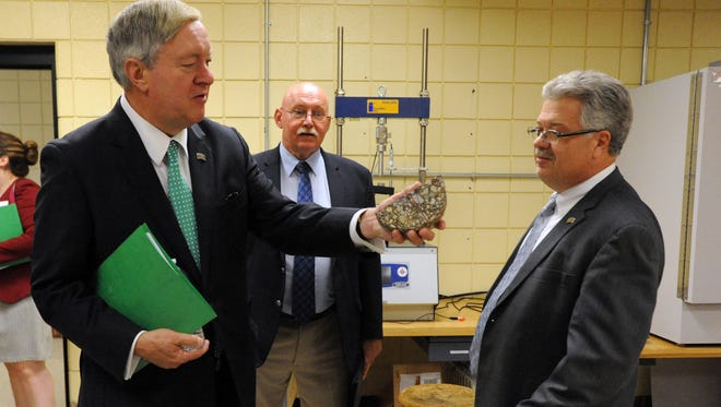 Ohio University President Duane Nellis, left, holds an asphault sample in his hand as he talks with Ohio University Lancaster Dean Jim Smith, right, in one of the regional campus's labs Wednesday, Aug. 9, 2017, in Lancaster. Also pictured is Bill Willen, executive director for the university's regional campuses.