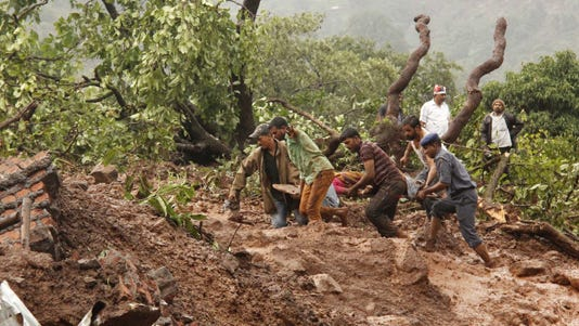 Rescue workers carry the body of a victim at the site of a landslide in Malin village, in the western Indian state of Maharashtra.