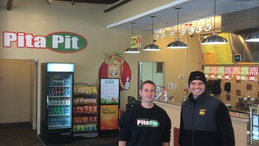 Mike Rink, left, opened a Pita Pit restaurant Dec. 7 in West Des Moines. He also plans to open a store on Ingersoll Avenue in January. He is pictured here with a customer.