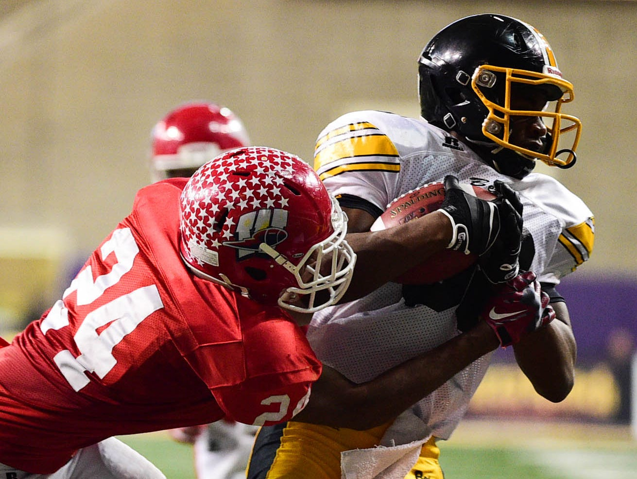 Bettendorf's Runningback Justin O'Conner (3) tries to get away from Cedar Rapids Washington's linebacker O'rien Vance (24) at the IHSAA Class 4A Football Semifinals held at the UNI-Dome in Cedar Falls, Iowa on Friday, Nov. 14, 2014.