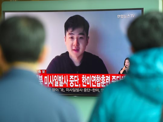 South Koreans watch a television news showing a video