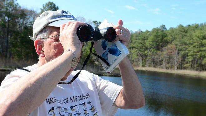 Larry Fry looks through a pair of binoculars at a marsh near Ocean Pines.