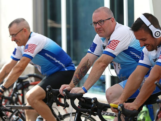 From left, Jim Rutkowski, from the St. Joseph County Sheriff's Department, Sgt. Mike Wilson, from the Indianapolis Metropolitan Police Department, and Sgt. Nathan Peach, from the Monroe County Sheriff's Department, cycle in place on Monument Circle for Cops Cycling for Survivors, an organization that raises awareness and funds for officers who have been killed in line of duty,  Friday, July 8, 2016.