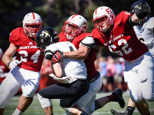 Jack Pietruszewski, Nathan Brinker and Peyton Thiry tackle St. Olaf quarterback Jack Goldstein during the Saturday, Sept. 17 game at Clemens Stadium in Collegeville.