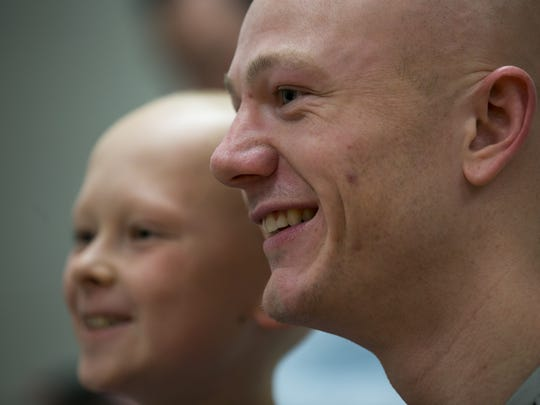 Trevor Lucas (right), poses for a photo with Braden Burkholder, 9, Brownsburg, both of whom have alopecia, during an event for people with alopecia before the night's men's basketball game against Manchester at Anderson University, Wednesday, Feb. 7, 2018. Alopecia is a medical condition that causes hair loss.