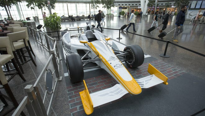 An Indy 500 car at Indianapolis International Airport announces the upcoming 100th anniversary of the race.