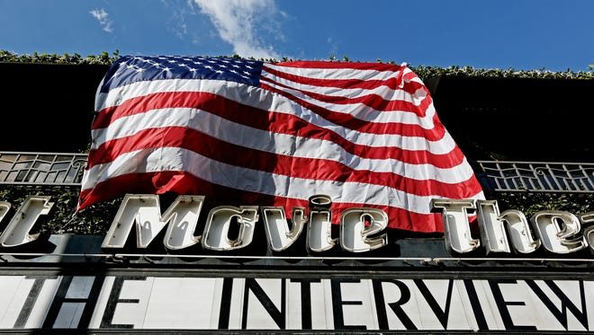 """The Interview,"" the comedy starring Seth Rogen and James Franco, is listed under an American flag on the marquee of the Cinefamily at Silent Movie Theater in Los Angeles on Christmas Day. The film's release was originally canceled by Sony after threats of violence by hackers linked to North Korea, but some independent theaters showed it."