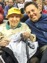 Mickey Kor, left, and his son, Alex Kor, went to the Crossroads Classic on Dec. 17 at Bankers Life Fieldhouse in Indianapolis. It was the last game Mickey Kor, a longtime season ticket holder at Mackey Arena, has been able to see in person while recovering from a series of illnesses in the past year. Mickey Kor, a Holocaust survivor, says Purdue games provided an escape from the memories of his time in a concentration camp.
