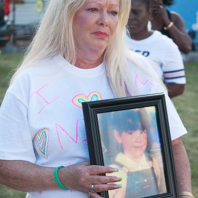 Robin Buonodono, holds a photo of her child, Nicole