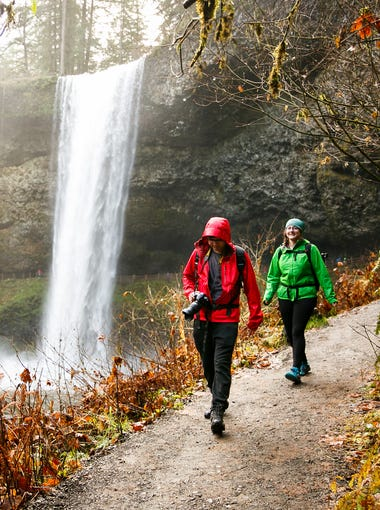"""Kathleen Herrin-Parmar, right, and her husband Swapnil Parmar, left, walk along the South Falls trail at Silver Falls State Park on """"Green Friday,"""" Nov. 24, 2017. Herrin-Parmar works for REI, and brought Parmar to Silver Falls for the first time as they took part in REI's #OptOutside initiative and Oregon Parks and Recreation's Green Friday campaign."""