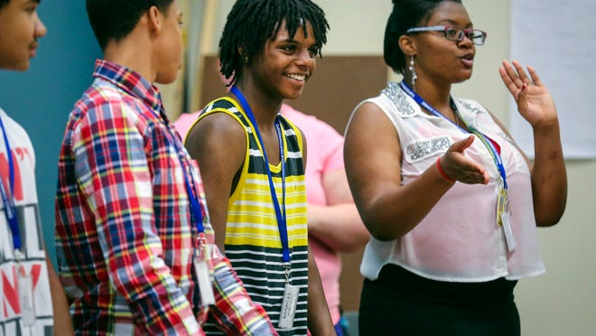 Marcel Burrage, center, smiles as he gets recognition from a fellow student during a program on Tuesday at the Evelyn K. Davis Center in Des Moines. Programs for at-risk, low-income kids help keep them occupied, safe and learning over the summer.
