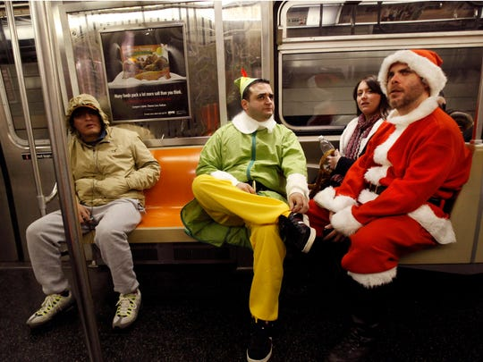 In this Dec. 11, 2010 file photo, John Paul, center, of Manhattan, dressed as an Elf and Michael Smallwood, of Brooklyn, dressed as Santa ride the E train downtown in New York for the annual SantaCon pub crawl where participants dress up in Santa and other Christmas themed outfits.