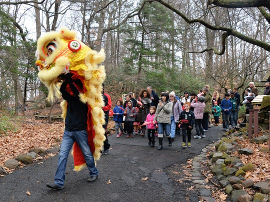 The parade begins!  Starting at the Cora Hartshorn Arboretum's historic Stone House, the ceremonial lion starts down the path on the journey to chase away bad spirits and to welcome spring.