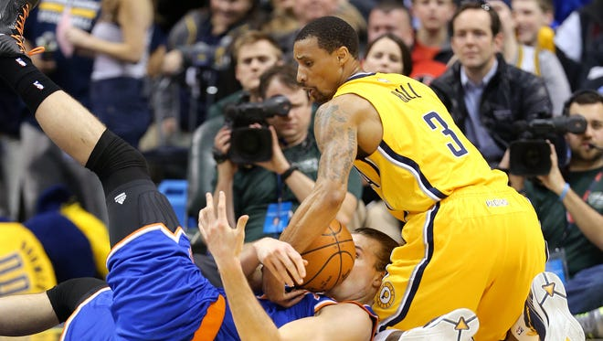 Pacers guard George Hill and New York's Lou Amundson battle for a loose ball in the first half of the game at Bankers Life Fieldhouse on Wednesday, Mar. 3, 2015.