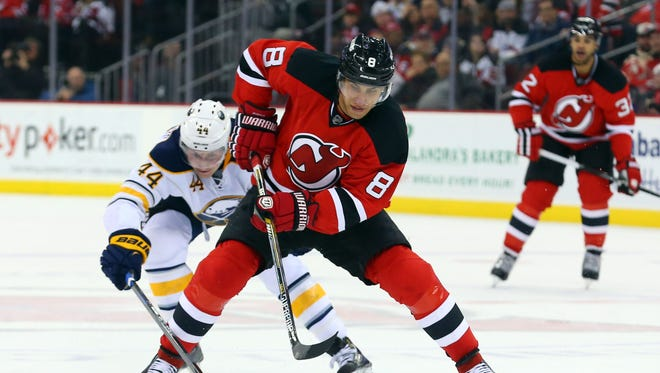 New Jersey Devils right wing Dainius Zubrus (8) skates with the puck while being defended by Buffalo Sabres left wing Nicolas Deslauriers (44) during the second period at Prudential Center.