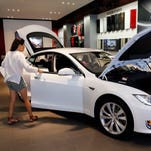 Customers mingle with ownership advisers in the Tesla Motors store in Pasadena, Calif. in this 2014 photo.