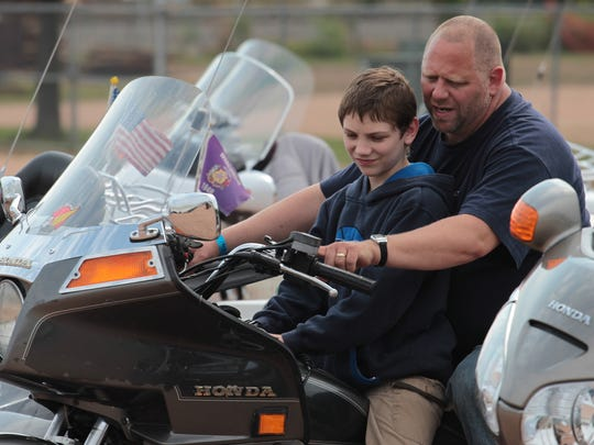 Mark Zehren gives his son Robbie Zehren, 13, a motorcycle lesson, at the 2013 Wisconsin District Convention of the Gold Wing Road Riders Association at Marathon Park in Wausau in 2012.