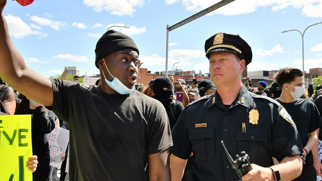 Protester Papee Paye of Worcester and Worcester police Capt. Matt D'Andrea talk after D'Andrea joined the march at the police station Sunday.